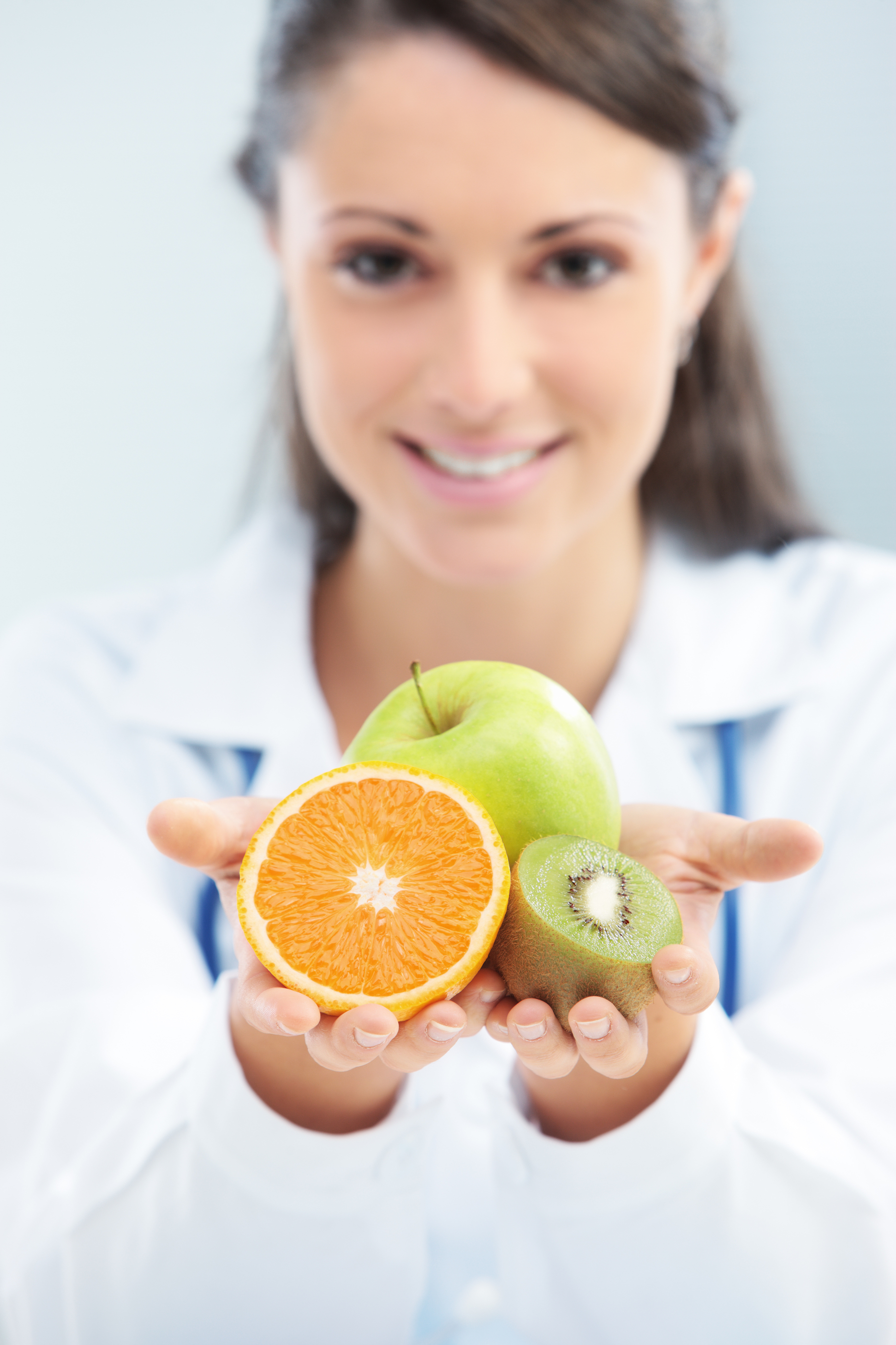 Nutritionist Doctor holding some fruits in her hand